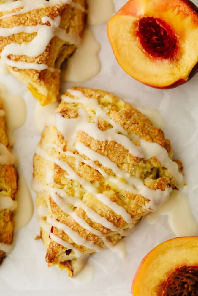 Up close picture of a peach scone with vanilla icing.