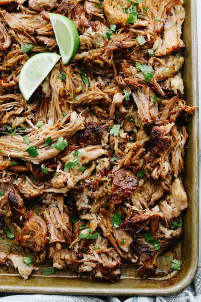 Shredded pork in a pan with a lime.