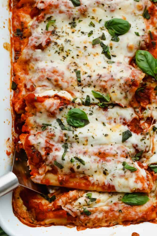 Manicotti being served with a serving spoon.