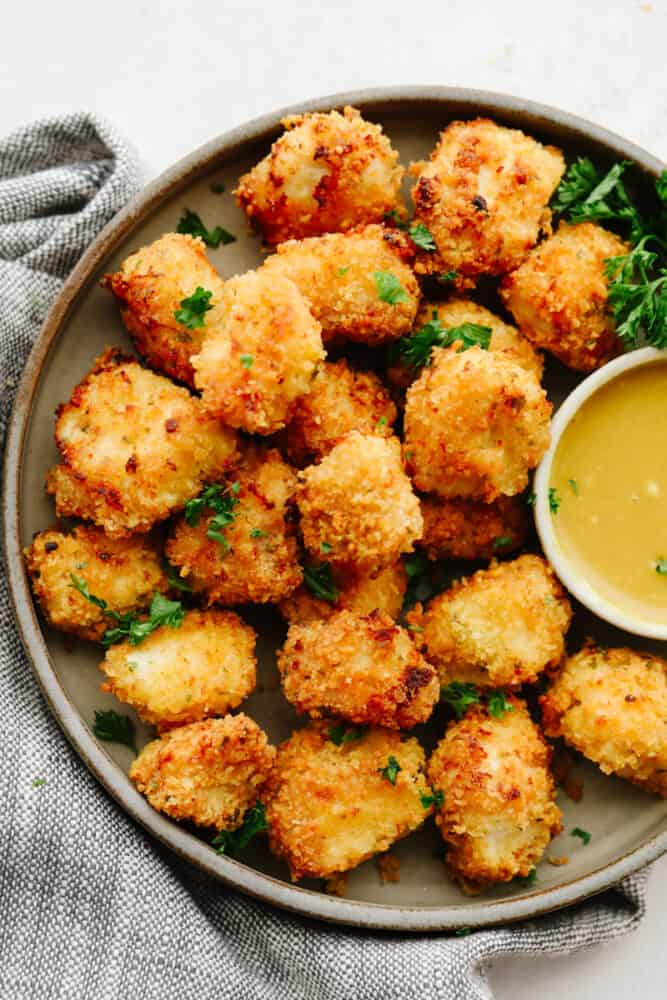 Chicken nuggets on a tray with honey mustard sauce.
